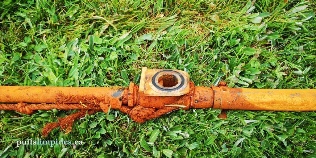 Résidus de boue d'eau ferreuse accumulés sur les équipements avant le nettoyage du puits.
